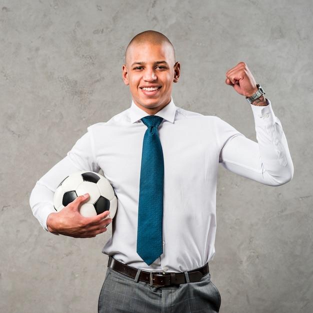 Joven empresario sosteniendo una pelota de fútbol en la mano apretando su puño de pie contra la pared gris Foto gratis