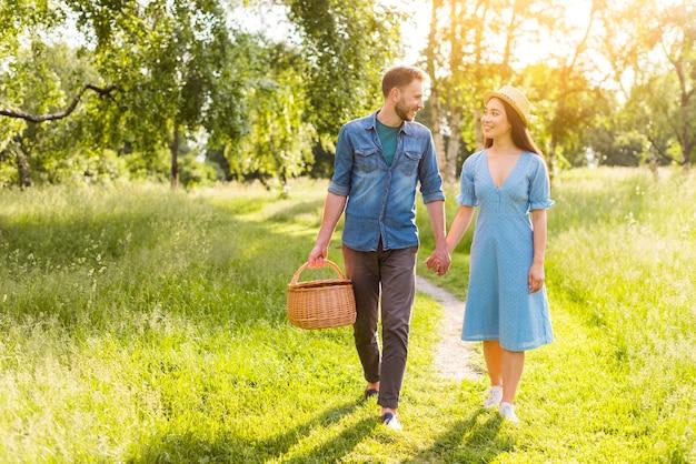 Joven enamorada multirracial caminando en el parque tomados de la mano Foto gratis