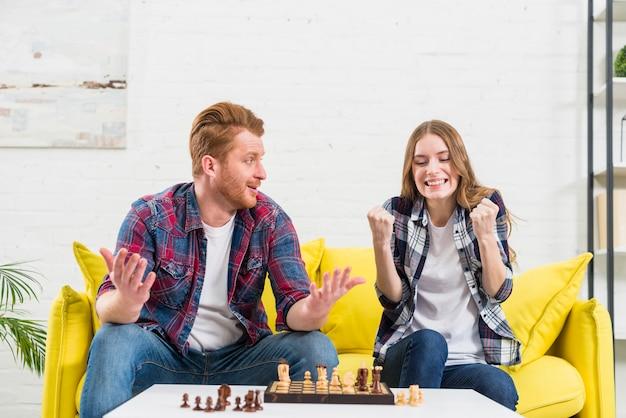 Joven encogiéndose de hombros y mirando a la novia apretando su puño con éxito después de ganar el juego de ajedrez Foto gratis