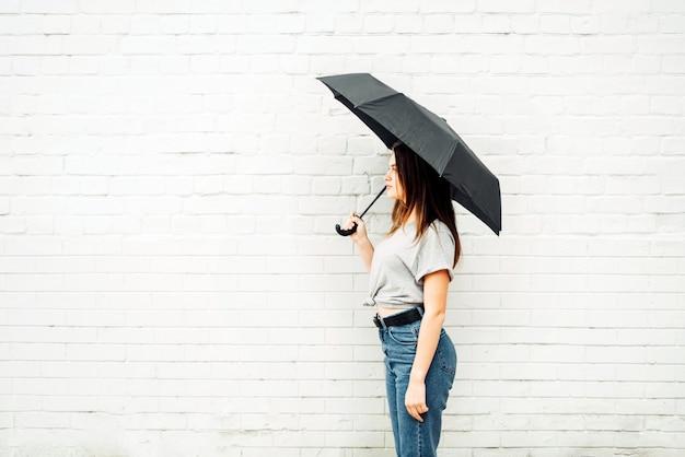 Una joven se encuentra con un paraguas negro Foto Premium