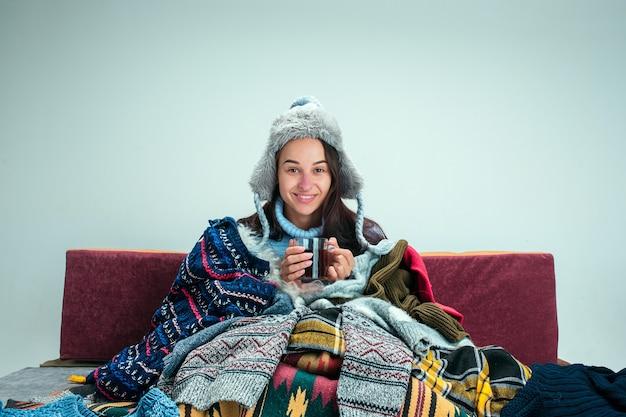 La joven enferma con chimenea sentada en el sofá en casa o estudio cubierto con ropa de abrigo tejida. enfermedad, influenza, concepto de dolor. relajación en casa. conceptos sanitarios. Foto gratis