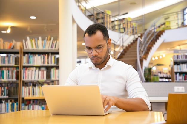 Joven enfocado escribiendo en la computadora portátil en la biblioteca pública Foto gratis
