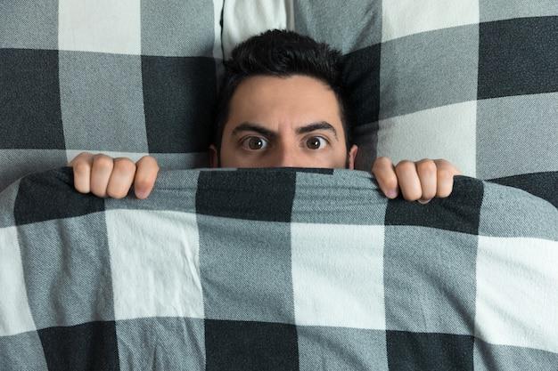 Joven escondido en la cama debajo de la manta en casa. Foto Premium