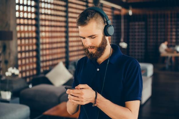 Joven escucha música en auriculares, usando teléfono inteligente, retrato de hipster al aire libre Foto gratis