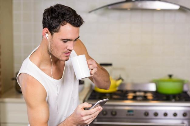 Joven escuchando música en casa en la cocina Foto Premium