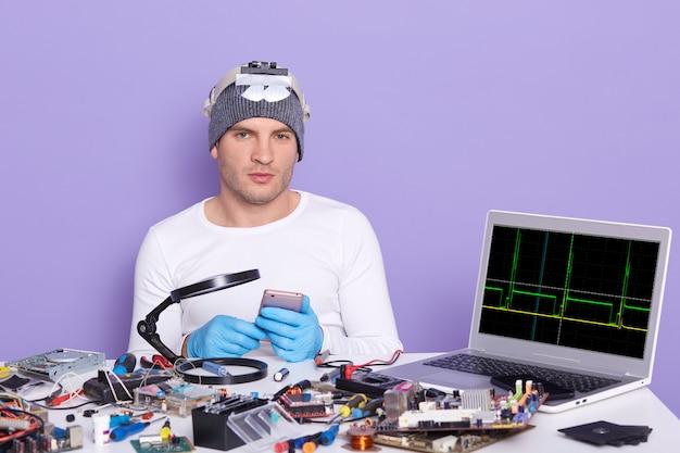 Joven especialista en computadoras que repara teléfonos inteligentes rotos, está listo para desmantelarlo, sentado en una mesa llena de herramientas, radiotrician probando equipos electrónicos en el centro de servicio. ingeniería electrónica Foto gratis