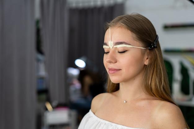 Joven esteticista niña caucásica tiene corrección de cejas modelo Foto Premium