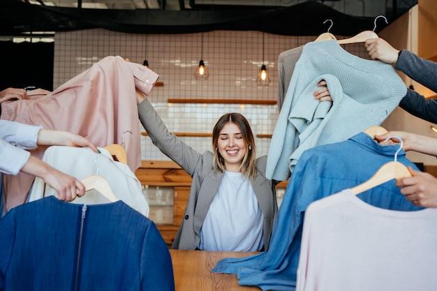 Joven estilista mirando a través de un conjunto de camisas para disparar a la moda Foto gratis