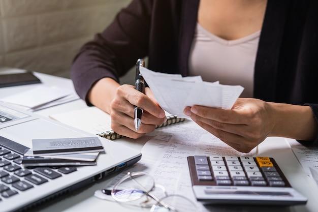 Joven estresada revisando facturas, impuestos, saldo de cuenta bancaria y calculando gastos en la sala de estar en casa Foto Premium