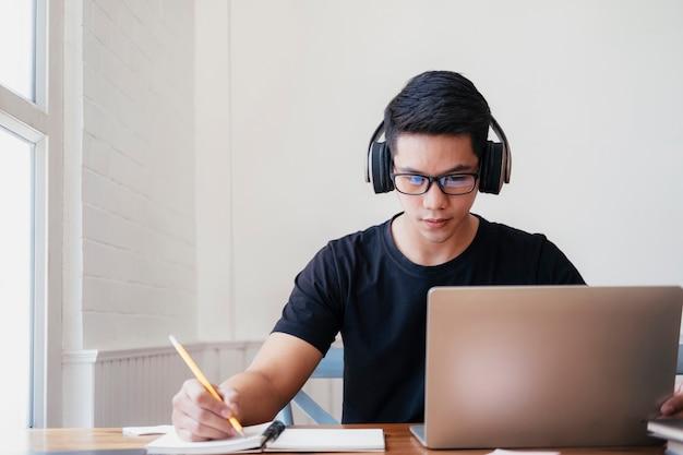 Joven estudia en casa usando una computadora portátil y aprende en línea Foto Premium