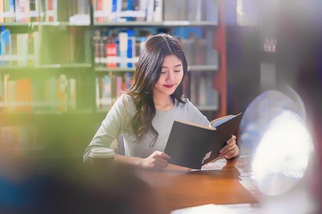Joven estudiante asiática en traje casual leyendo un libro con una taza de café en la biblioteca Foto Premium