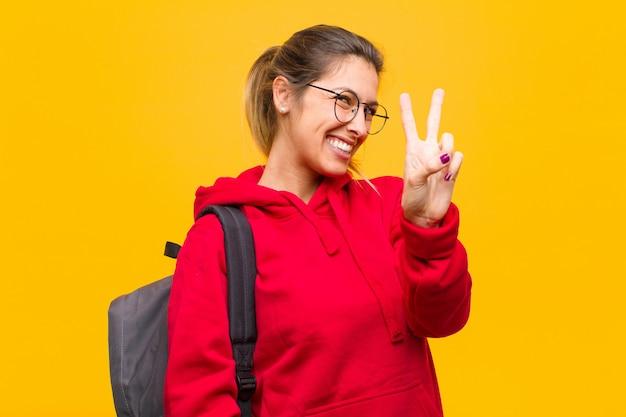 Joven estudiante bonita sonriendo y mirando amigable, mostrando el número dos o segundo con la mano hacia adelante, contando hacia atrás Foto Premium