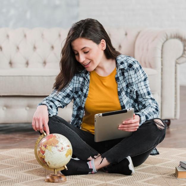 Joven estudiante inteligente usando un globo terráqueo Foto gratis
