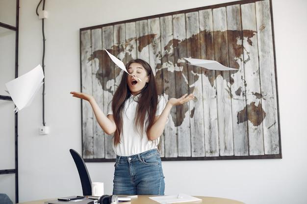 Joven estudiante de pie en la oficina y arroja los documentos Foto gratis