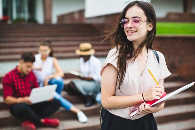 Joven estudiante posando con bloc de notas Foto Premium