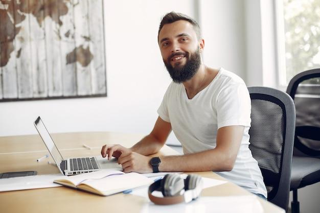 Joven estudiante sentado en la mesa y usar la computadora portátil Foto gratis