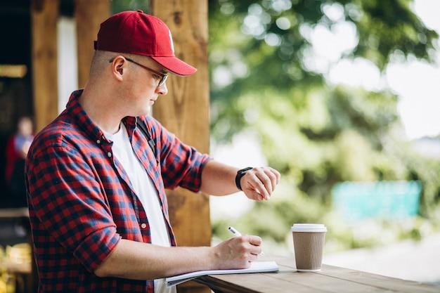 Joven estudiante trabajando en una cafetería en el parque Foto gratis