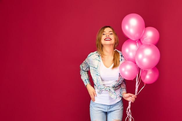 Joven excitada posando con globos rosados Foto gratis