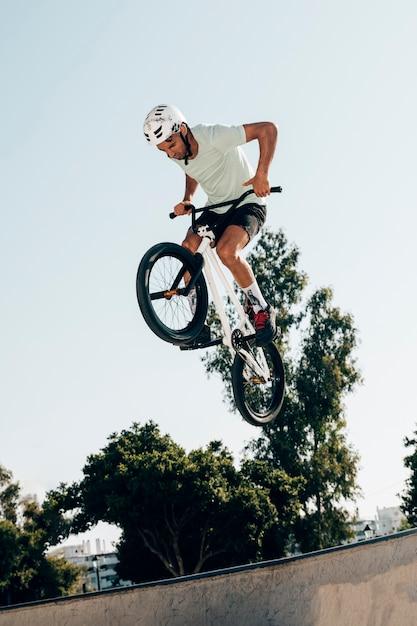 Joven extremo saltando con bicicleta vista de ángulo bajo Foto gratis