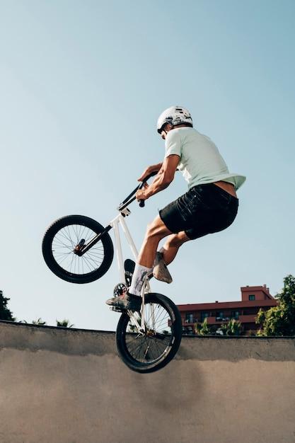 Joven extremo saltando con bicicleta Foto gratis