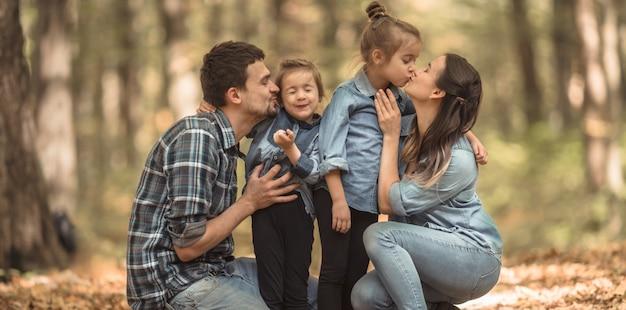 Una joven familia camina en el bosque de otoño con niños. Foto Premium