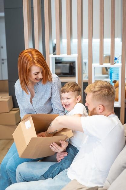 Joven familia feliz con niño desempacando cajas juntos sentados en el sofá Foto gratis