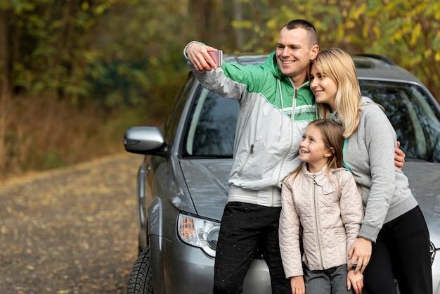 Joven familia feliz tomando una selfie en la naturaleza Foto gratis