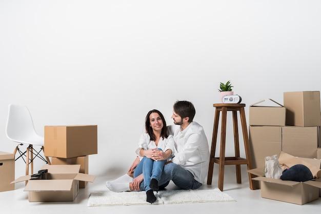 Joven familia junta en piso nuevo Foto gratis
