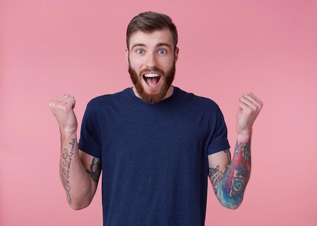 Joven feliz barbudo rojo con ojos azules, boca muy abierta con deleite, celebra la victoria de su equipo de fútbol favorito, con los brazos levantados y los puños cerrados, aislado sobre fondo rosa. Foto gratis