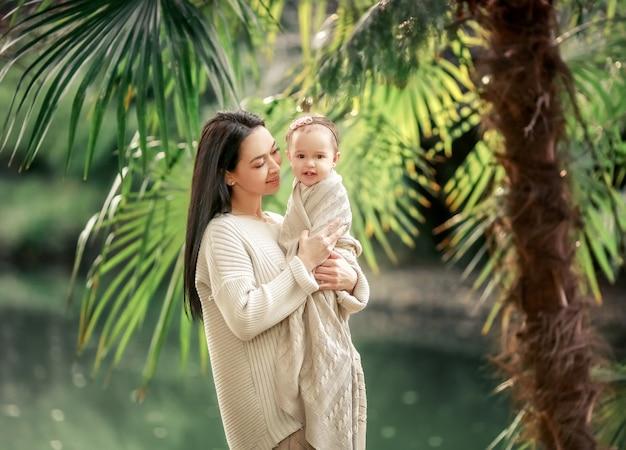 Joven y feliz madre cuida a su pequeño hijo y camina por la orilla del lago en el verano en el parque Foto Premium