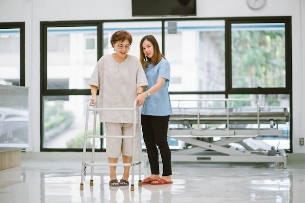 Joven fisioterapeuta ayudando a un paciente mayor a usar el andador durante la rehabilitación Foto Premium