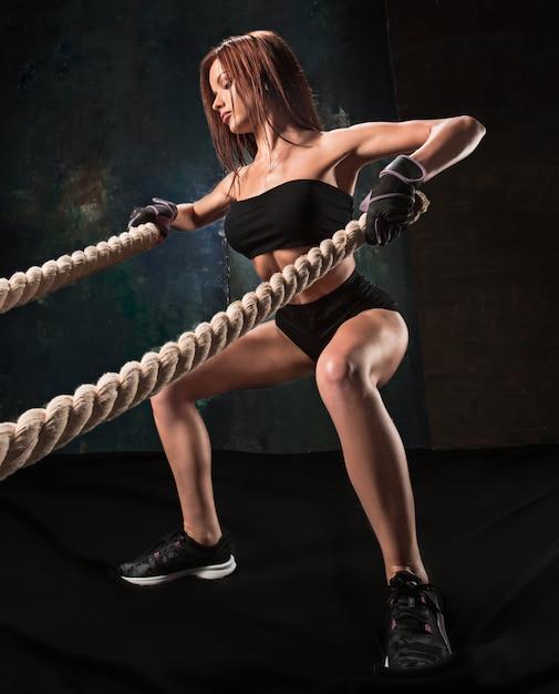 La joven fuerte tirando de la cuerda en un gimnasio Foto gratis
