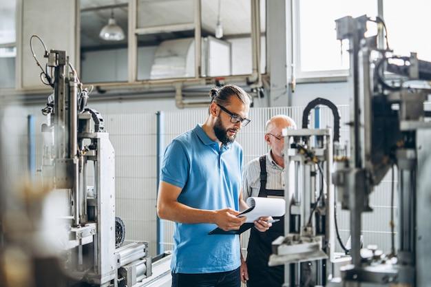 Joven gerente con barba mostrando e inspeccionando el proceso de trabajo del trabajador profesional adulto en la gran fábrica. Foto Premium
