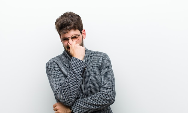 El joven gerente se siente disgustado, tapando la nariz para evitar oler un hedor desagradable y desagradable sobre la pared blanca Foto Premium