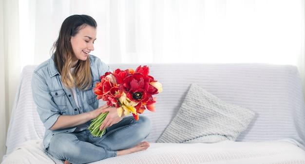 Una joven con un gran ramo de tulipanes sentada en el sofá de la sala de estar. Foto gratis