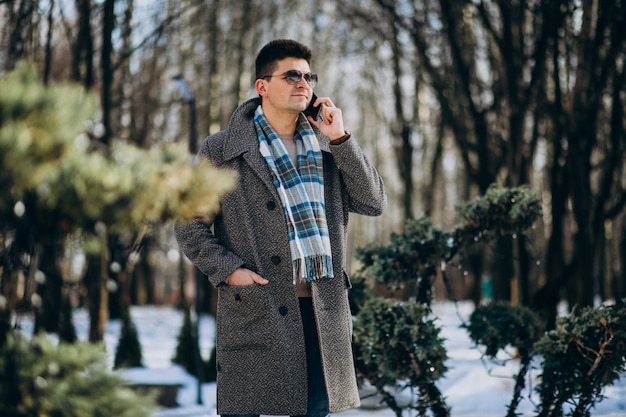 Joven guapo afuera usando el teléfono Foto gratis