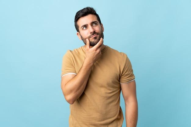 Joven guapo con barba sobre pared aislada teniendo dudas Foto Premium