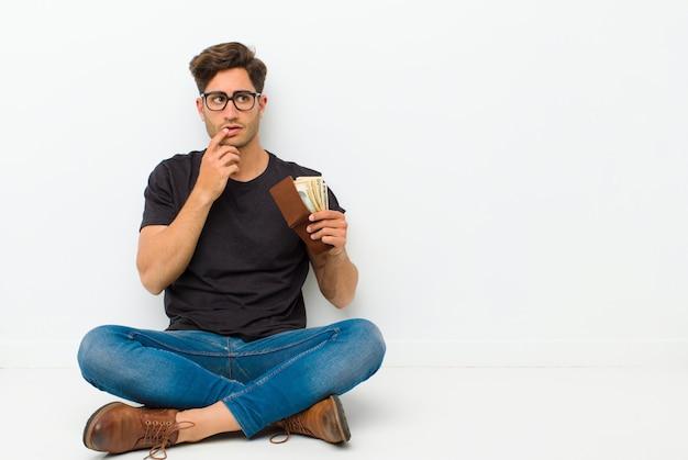 Joven guapo con una billetera sentada en el suelo sentada en el suelo en una habitación blanca Foto Premium