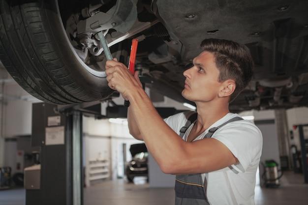 Joven guapo mecánico reparando el vehículo en su garaje Foto Premium