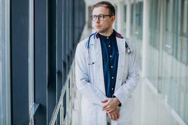 Joven guapo médico con estetoscopio en clínica Foto gratis