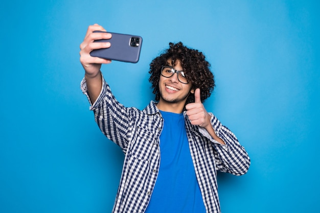 Joven guapo rizado haciendo una selfie sobre pared azul aislada Foto gratis