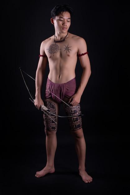Joven guerrero masculino de tailandia posando en una posición de combate con un arco Foto gratis