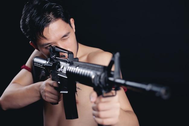 Joven guerrero masculino de tailandia posando en una posición de combate con un arma de fuego sobre negro Foto gratis