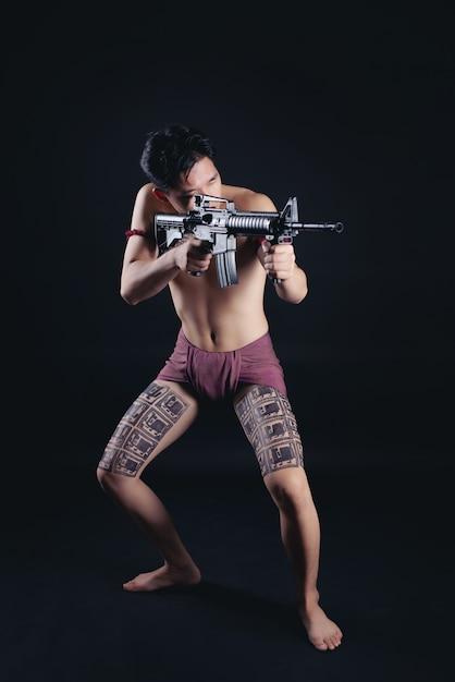 Joven guerrero masculino de tailandia posando en una posición de combate con un arma de fuego Foto gratis