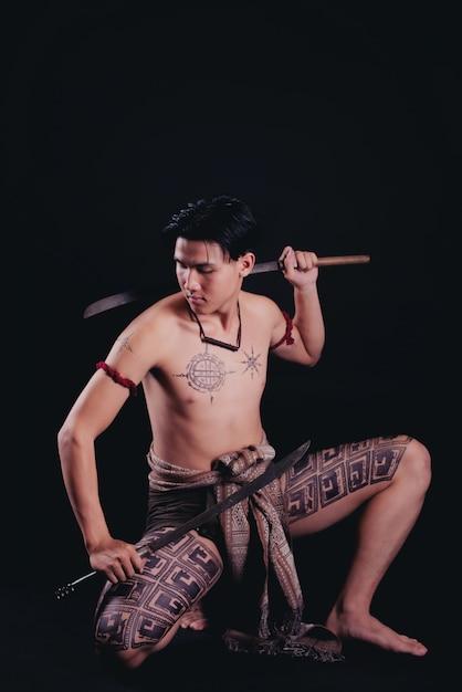 Joven guerrero masculino de tailandia posando en una posición de combate con una espada Foto gratis