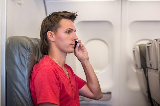 Joven hablando por teléfono dentro del avión Foto Premium