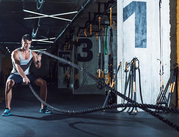 Joven haciendo ejercicio con cuerdas de batalla Foto gratis