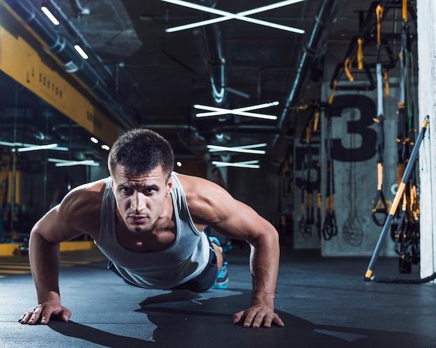 Joven haciendo flexiones en el gimnasio Foto gratis