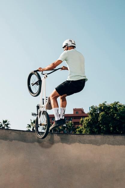 Joven haciendo trucos en su bicicleta Foto gratis