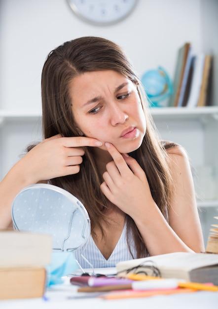 Joven hembra es exprimir una espinilla antes de maquillaje Foto gratis